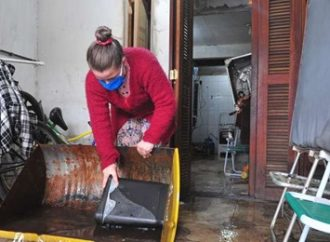 Moradores trabalham para limpar casas no bairro Humaitá, em Porto Alegre